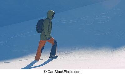 girl traveler hiking in winter mountains, trekking in wintertime, snowy weather