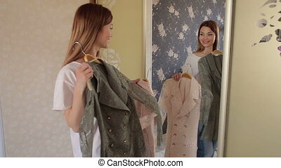 Girl tries on a pink and grey jacket at home in the bedroom near a large mirror.