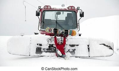 Girl try to improve her snowboarding near snowcat - Girl try...