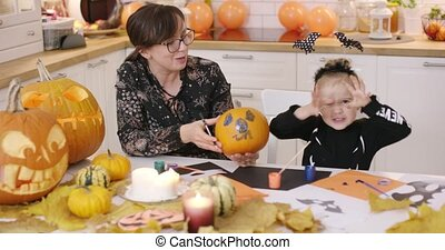 Girl trying to be scary - Woman in glasses holding pumpkin...
