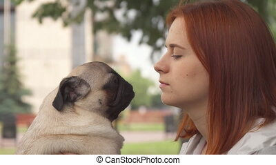 Girl trying to kiss her pug and looking at camera