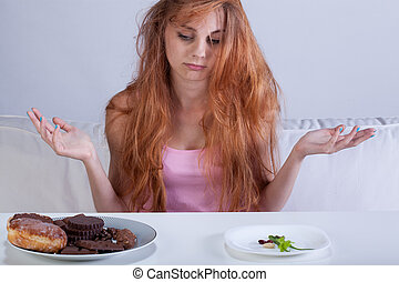Girl trying to overcome hunger for sweets - Young girl...