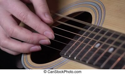 Girl trying to play guitar, close up