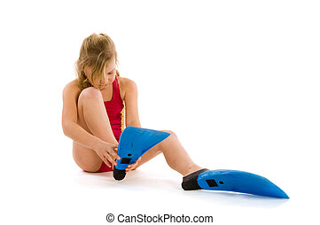 Girl trying to put on flippers - Girl with blond hair trying...