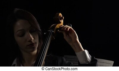 Girl tunes a cello. Black background. Close up - Girl in a...