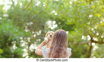 Girl turns a puppy on hands