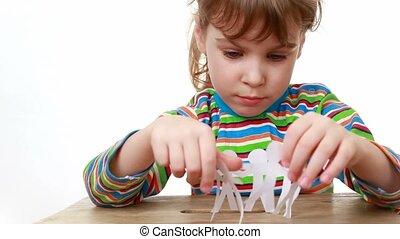 girl turns a ribbon of paper cut manikins in circle