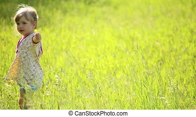 Girl turns around in the grass
