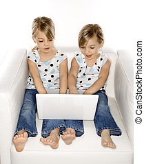 Girl twins with laptop computer.