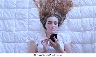 Girl types a message on mobile lying on bed top view