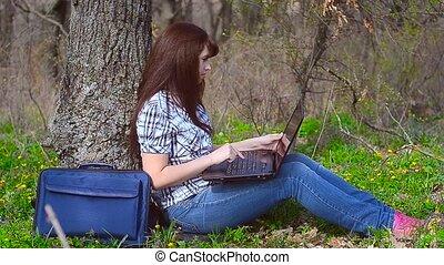 Girl typing on a keyboard sitting at laptop