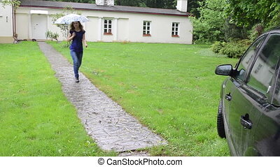 Girl with umbrella walk through cobbled path in strong rain and sit in car.