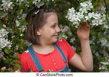 Girl under a blooming apple tree
