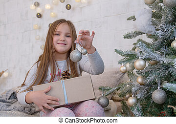 Girl under Christmas tree with ball