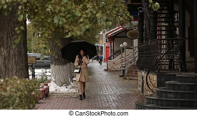 Girl under umbrella walking and talking on the phone