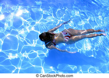 Girl in bikini swimming underwater in blue swimming pool