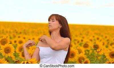 Girl undresses in sunflowers.