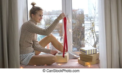 Girl unpacks a gift while sitting