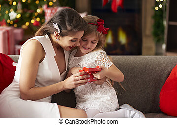 Girl unwrapping Christmas gift box with mummy