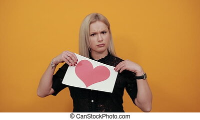 Beautiful blonde girl in black dress on yellow background upset unhappy woman holding piece of paper with red heart palm of hand stops