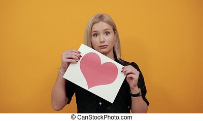 Beautiful blonde girl in black dress on yellow background upset woman dissatisfied holding piece of paper with red heart