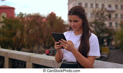 girl use touch screen tablet outdoors
