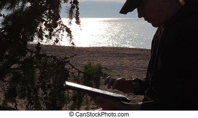 Girl uses a tablet on the Baikal beach