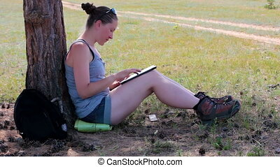 Girl uses a tablet, sitting under a tree in a field