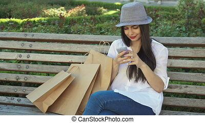 Girl uses her smartphone on the bench