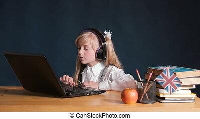 Girl Uses Laptop - Focused schoolgirl using laptop in the...