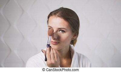 Girl Uses Makeup Brush - Lovely girl in the white bathrobe...