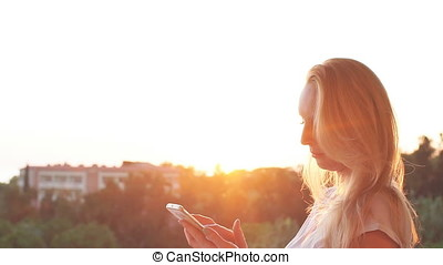 Girl uses smartphone by the sea on the sunset. Slow motion
