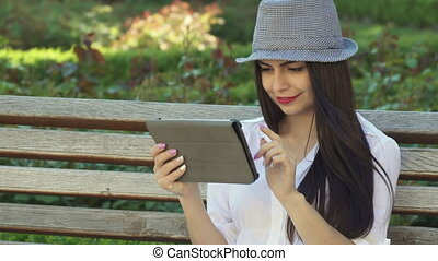 Girl uses tablet on the bench