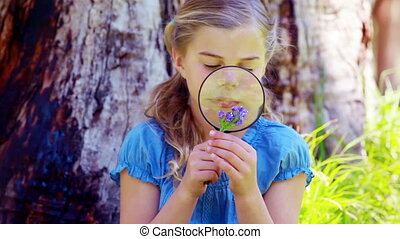 Girl using a magnifying glass in a park