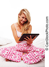 Girl using a tablet on her bed