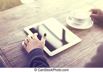 Girl using digital tablet and a cup of coffee on a wooden table