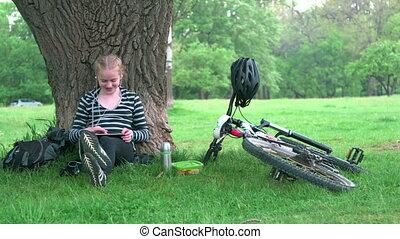 Girl using digital tablet computer in park