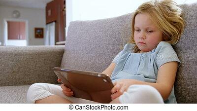 Girl using digital tablet in living room 4k - Girl using ...