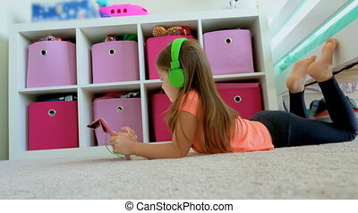 Girl using digital tablet on floor at home 4k