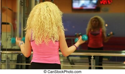 girl using dumbles in a gym 2