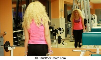 girl using dumbles in a gym 4
