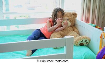 Girl using glass digital tablet on bed in bedroom 4k