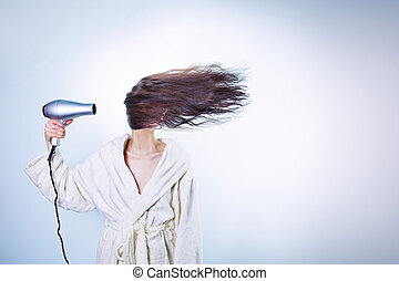 girl using hair dryer at full speed