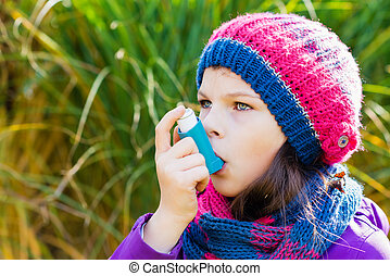 Girl Using Inhaler on a autumn day - to Treat Asthma Attack....