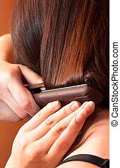 Girl using iron on her hair