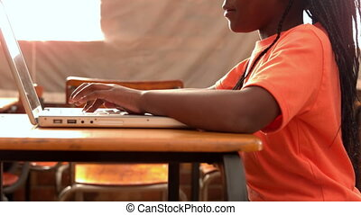 Girl using laptop in classroom