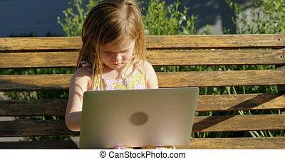 Girl using laptop in the garden 4k