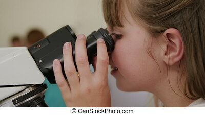 Girl using microscope - Close up of a Caucasian girl sitting...