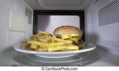 Double hamburger with french fries reheating inside microwave oven