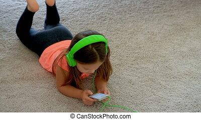 Girl using mobile phone on floor at home 4k - Cute girl...
